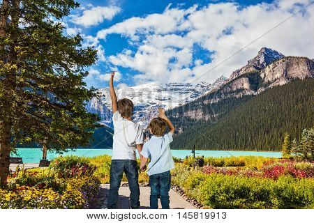 Lake Louise in Banff National Park in the Canadian Rockies. Two lovely slender boys admire the beauty of the glacial lake
