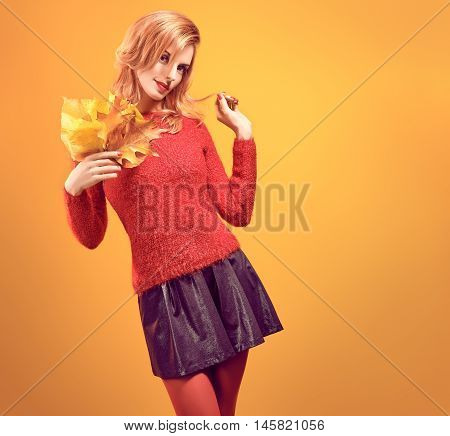 Fall Fashion. Model Woman in Autumn Fashion Outfit. Playful Beauty Redhead girl in Stylish fashion Sweater with autumn leaves smiling. Trendy Hairstyle, Makeup. Fall Autumn fashion. Creative Vintage