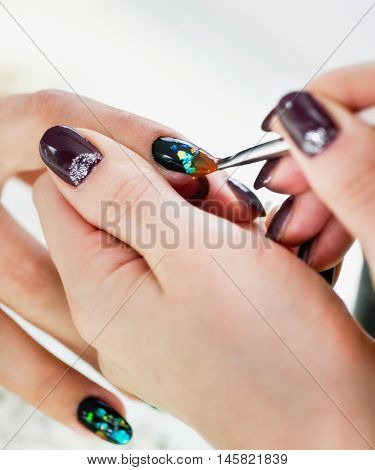 Painting fingernails in nail salon, close up