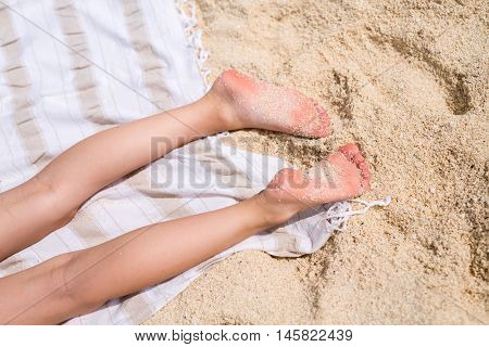 Close up of a little girl legs on a beach towel