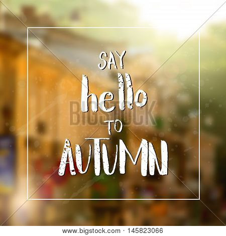 Say hello to autumn. Handwritten autumn greeting card. Modern calligraphy on blurred background.