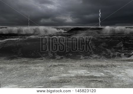 Dark ocean in storm with lightening and waves flooding concrete ground.