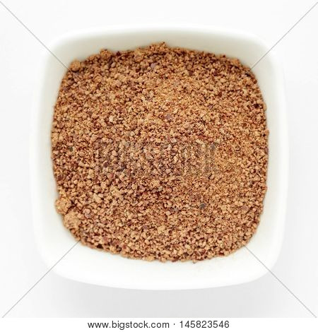 Organic powder of Indian Jujube (Ziziphus mauritiana) in a white ceramic bowl. Isolated on white background. Top view.