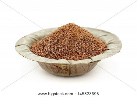 Organic powder of Indian Jujube (Ziziphus mauritiana) in a natural leaf plate. Isolated on white background. Front view.