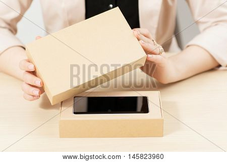 Woman opening box with new smartphone, close-up. Female customer lifting lid from package with her order. Delivery service. online shopping, parcel opening , gift concept