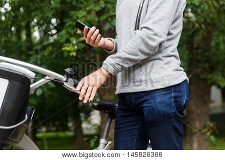 Guy in blue jeans standing next to his bike and holding cell phone