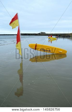 Red and yellow flag on the beach in Lyme Regis indicating area patrolled by lifeguards