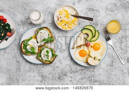 Delicious breakfast - fried egg poached eggs avocado cheese sandwiches spinach salad muesli milk and orange juice on light surface top view