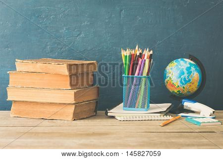 School books colored pencils notebook stapler calculator and globe on a wooden table
