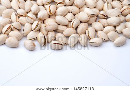 Roasted and salted pistachios in shell on white background.