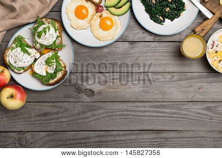 Helpful and tasty breakfast from different of dishes - fried egg poached eggs avocado apple spinach salad muesli and orange juice on wooden table with copy space top view