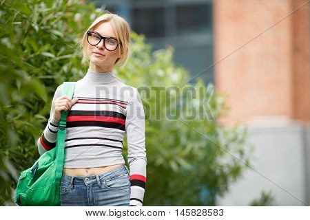 dreamy girl in glasses stands in front of building on background of Bush