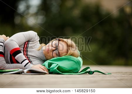 tired student spectacled fell asleep for textbooks in yard