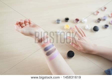 Female hand with colorful eyeshadow smears, visagiste pov. Makeup artist testing colors of decorative cosmetics, top view on swatches