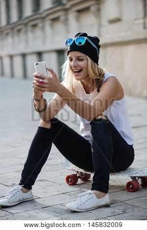 Hipster girl using mobile oudoor