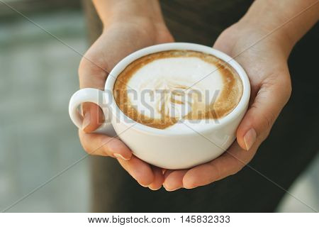 A cup of Cappuccino in female hands on blurred background. The concept of relaxing in the cafe, relaxing time in a cafe, dreams of love, etc.