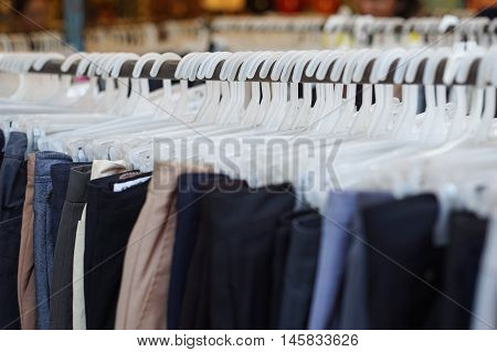 close up a lot of rack of clothes hanging in a row on shelf selective focus