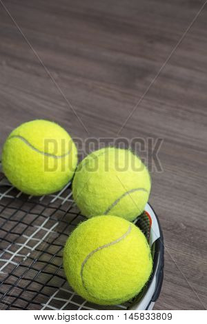 Usual tennis racquet with three green balls on the wooden background