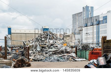 Metallic waste solution dump pile in the yard of a factory with big furnace and processing unit in the background