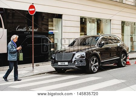 PARIS FRANCE - MAY 21 2016: Man taking photo of the luxury Bentley Bentayga Hybrid SUV on the streets of Paris France