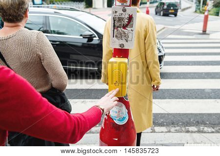 LUXEMBOURG LUXEMBOURG - JUN 5 2016: Woman pressing button to cross the street in crowded area in the city of Luxembourg