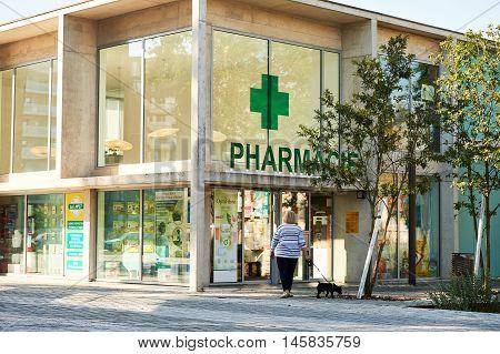 STRASBOURG FRANCE - AUG 21 2015: Adult woman with dog walking toward pharmacie