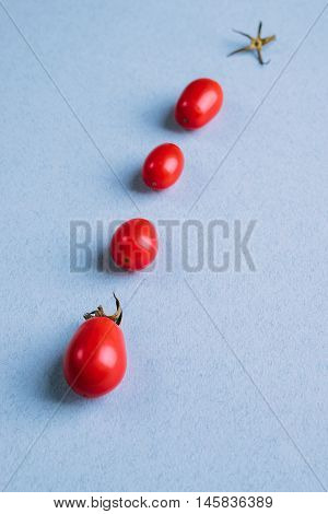 Four Red Tomatoes On A Blue Table