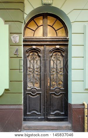 Old wooden doors with stained-glass windows forged grills and ornaments. Architectural details for background.