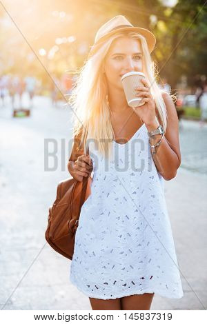 Young beautiful blonde girl in hat drinking coffee from take away cup while walking on the street