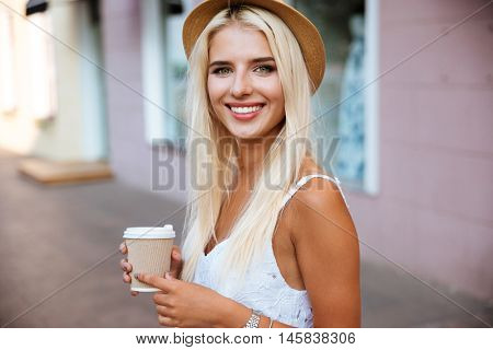 Close up portrait of a smiling young girl in hat holding take away coffee cup outdoors
