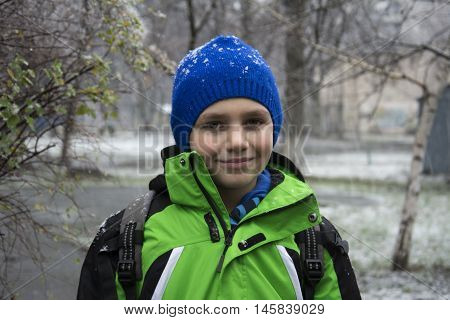 In the winter on the street under a cloudy sky boy standing under falling snow.
