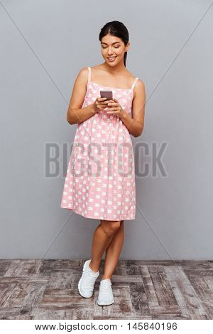 Full length portrait of a happy young girl using smartphone isolated on a gray background