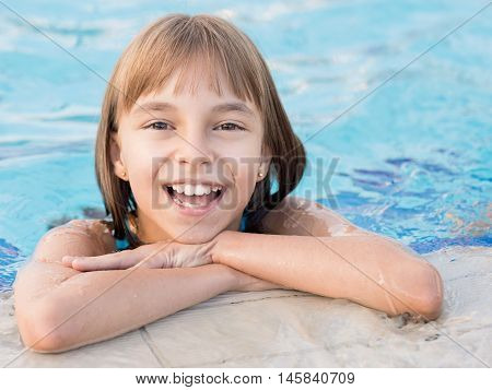 Close-up portrait of happy girl in the swimming pool at aquapark. Cute child having fun enjoyable time on vacation. Looking at camera.