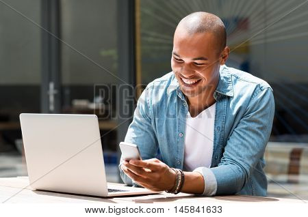 Young happy man smiling and holding a smartphone sitting outdoor with laptop. Portrait of laughing african guy reading a message with smartphone in cafe. Man smiling and writing a phone message.
