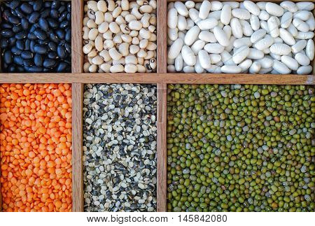 Collection assorted of lentils beans peas grain groats soybeans legumes in wooden box