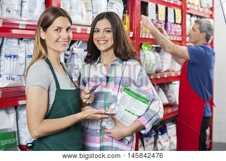 Saleswoman Accepting Payment From Customer In Pet Shop