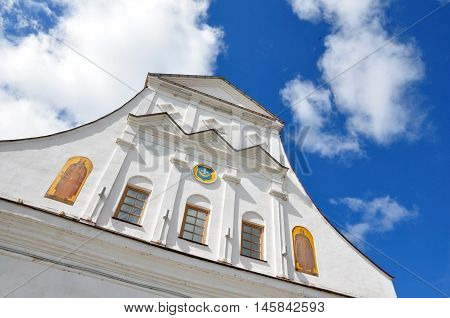 Old Town Hall in Orsha, Belarus. The white facade with decor in the Baroque style and coat of arms against the blue sky with clouds. Look up.