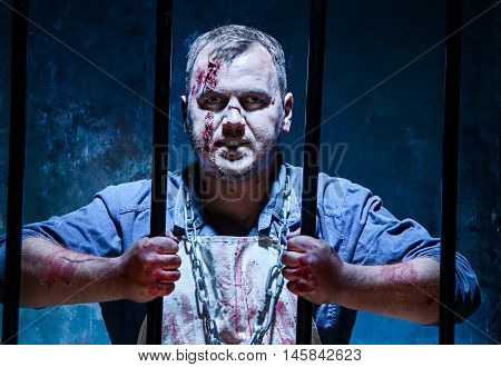 Bloody Halloween theme: crazy killer as bloody butcher on dark blue background