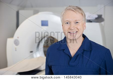 Professional Standing By MRI Machine In Clinic