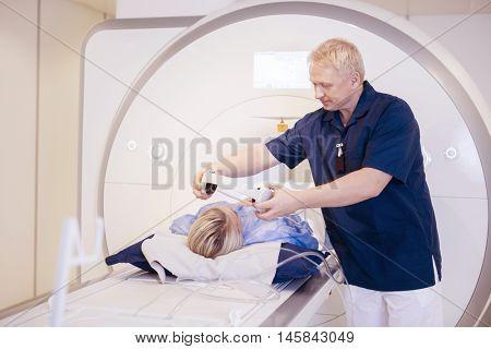 Radiologist Putting Headphones On Female Patient Undergoing MRI