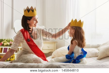 Happy loving family is preparing for a costume party. Mother and her child girl playing together. Beautiful queen and princess in gold crowns.