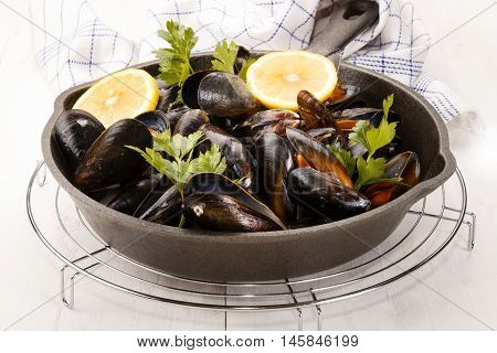 cooked scottish mussels with parsley and lemon in a cast iron pan