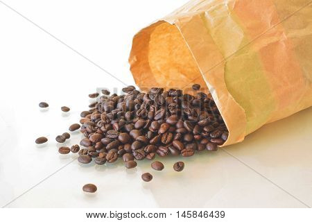 Roasted Coffee Beans With Paperbag Scattered Isolated On White Background.