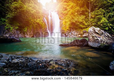 Traveling in the spring forest and new discovery waterfalls. Beautiful waterfall in spring forest with sunlight.