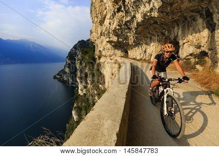 Woman biking on Sentiero della Ponale, Riva del Garda, Italy. Amazing view of Lake Garda in background.
