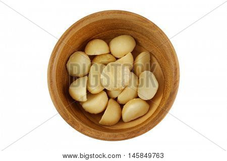 Top view of roasted salted Macadamia nuts with salt in wooden bowl isolated on white background.
