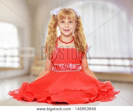 A beautiful little Caucasian girl with long, blonde ponytails on her head in a bright orange dress . Sat down on the floor.In a room with a large semi-circular window.