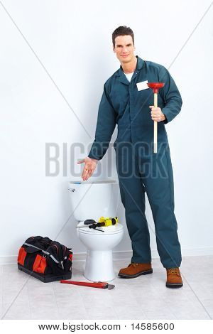 Young plumber releasing stoppage in the flush toilet