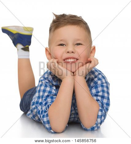 Happy little boy in shirt and shorts lying on the floor. He put his head in his hands and looks straight into the camera - Isolated on white background