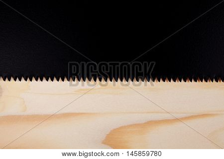 Black saw over a wooden background with space for text. Carpenter workplace top view